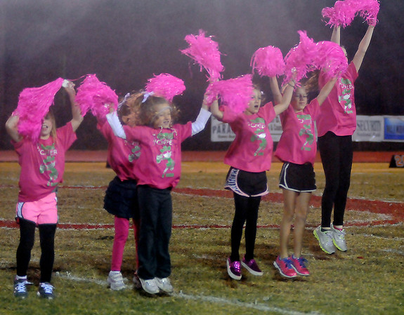 Heavy rain begins to fall as the OBA Mini-Cheerleaders entertain during half time of the Trojans' game against the Okeene Whippets at Commitment Field Friday. (Staff Photo by BONNIE VCULEK)