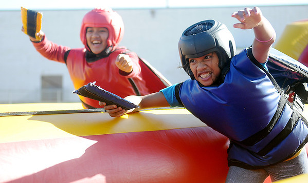 Joleina Kejlat (right) lunges ahead of Erna Nenam as they race on the Bungee Run during The Commons' Oktoberfest activities Friday. (Staff Photo by BONNIE VCULEK)