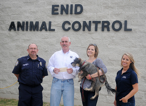 """Whitney Box holds Jasmine """"Jazz"""" Box Saturday as she presents a $500 donation to Allen Elder, EPD Chief Brian O'Rourke (from left) and Rachel Hancock (right). The donation was made in memory of Box's brother, Austin, who loved the City of Enid Dog Park and efforts to help dogs, like puppy """"Jazz"""" that he rescued from a dumpster. (Staff Photo by BONNIE VCULEK)"""