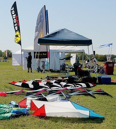 Lines of kites cover the grass near a competition field Tuesday. (Staff Photo by BONNIE VCULEK)