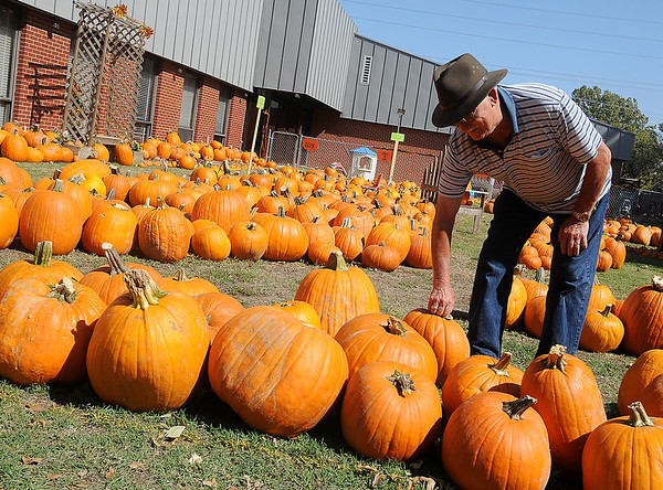 Boone Davidson arranges pumpkins at Christ United Methodist Church's Pumpkin Patch Wednesday. More than 40,000 lbs. of pumpkins, priced from under a $1.00 - $55.00, are available to area residents for their holiday baking and decorating needs. (Staff Photo by BONNIE VCULEK)