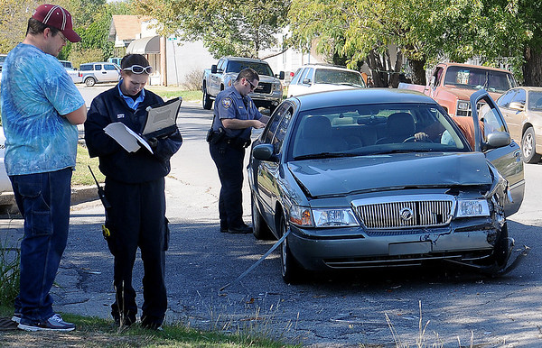 As a Life EMS responder (left) gathers information on an accident victim before transporting the individual to a local hospital, an Enid Police Department officer investigates the scene of a two-vehicle accident at Randolph and Tyler Saturday. (Staff Photo by BONNIE VCULEK)