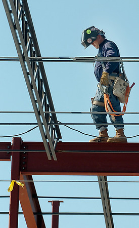 A welder walk a beam Monday as construction continues on the University Center at Enid High School. (Staff Photo by BILLY HEFTON)