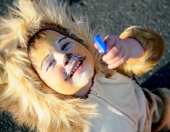 McCoy Landwehr, a friendly lion, holds up one of his candy bars during Scare on the Square on the Garfield County Courthouse lawn Saturday. Thousands of pounds of candy were distributed to youngsters during the annual event in downtown Enid. (Staff Photo by BONNIE VCULEK)
