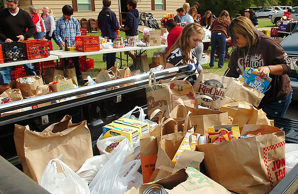 Volunteers unload a pick-up of donated food Sunday during the fall food drive for Horn of Plenty. (Staff Photo by BILLY HEFTON)