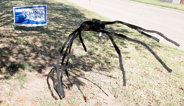 A giant, red-eyed spider swings in the gusty wind Thursday near a Romney/Ryan campaign sign. (Staff Photo by BONNIE VCULEK)