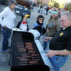 Garfield County Reserve Deputy Butch Phillips prepares the last of 800 hot dogs during Scare on the Square Saturday at the Garfield County Court House. (Staff Photo by BONNIE VCULEK)