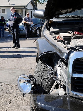 Damage is visible on two vehicles Saturday as an Enid Police officer investigates the accident scene at Randolph and Tyler before Life EMS transports and injured individual to a local hospital. (Staff Photo by BONNIE VCULEK)