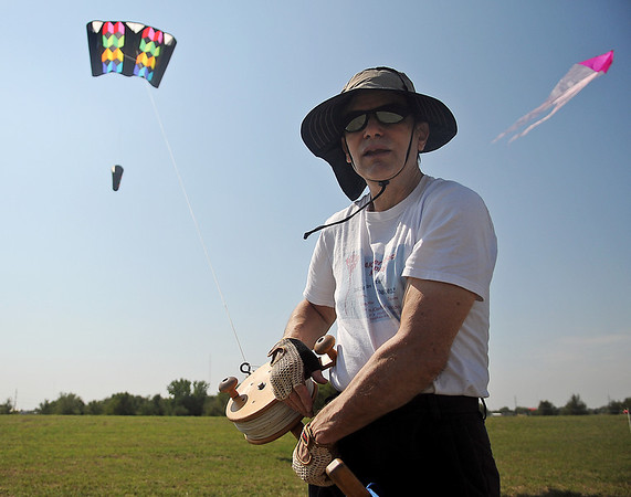 Brian C. Slater, an American Kite Association Certified Kite Pilot from East Hartford, Connecticut, uses a Strata Spool with 1,000 feet of 300 pound test line to fly his 30 square foot sled kite (above left) Monday during the AKA National Convention in Enid. (Staff Photo by BONNIE VCULEK)