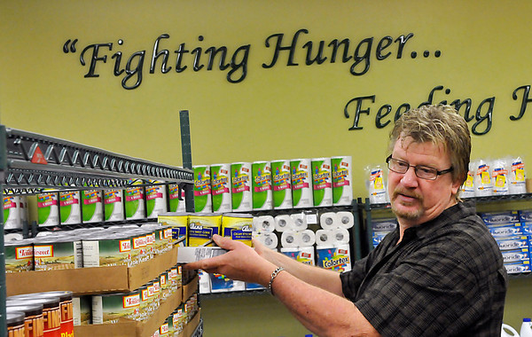 Al Fields stocks shelves at Loaves & Fishes Monday in preparation for the grand opening of the food resource center. (Staff Photo by BILLY HEFTON)