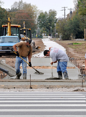 Workers smooth out concrete for the trail system Wednesday as it reaches Van Buren. (Staff Photo by BILLY HEFTON)