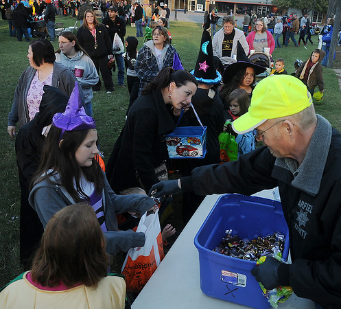 Bill Winchester, former Garfield County Sheriff, hands more than 100 pounds of candy out to trick or treaters Saturday during Scare on the Square. (Staff Photo by BONNIE VCULEK)