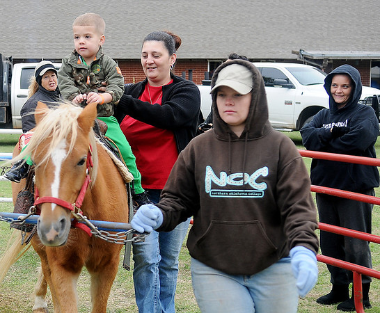 A young boy gets a helping hand from his mother as he rides a pony during the 5th annual Oktoberfest Celebration at Redeemer Lutheran Church Saturday. (Staff Photo by BONNIE VCULEK)