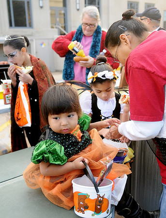 Ahiya, Gabriela and Annette Lara (front, from left) finish their hot dogs during Scare on the Square Saturday at the Garfield County Court House. (Staff Photo by BONNIE VCULEK)