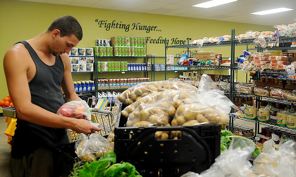 Derek Parks, a volunteer at Loaves & Fishes NW Oklahoma, takes a little time to shop at the client pantry Thursday. The grand opening of the non-profit location at 701 E. Maine is slated for Oct. 23 at 11 a.m. Tours of the facility will run until 2:30 p.m. (Staff Photo by BONNIE VCULEK)