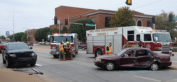 Enid Fire Department responds to an accident scene at the intersection of W. Owen K. Garriott and S. Independence Friday. The driver of the vehicle (right) was transported to a local hospital by Life EMS. (Staff Photo by BONNIE VCULEK)