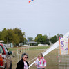 Brylie Burns flies a small sled kite with the help of her great grandmother Norina Wehrenberg during the American Kitefliers Association National Convention mass ascension Thursday. (Staff Photo by BONNIE VCULEK)