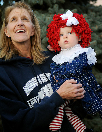 Glenda Aebi (left) holds the cutest Little Raggedy Ann Doll, Reese Lenherr, (right) as they glance toward the sky during Scare on the Square at the Garfield County Courthouse Saturday. Reese Lenherr was one of the three costume contest winners in the 0-4 year old category. (Staff Photo by BONNIE VCULEK)
