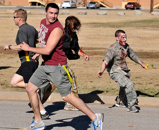 A runner looks back after making his way through a line of zombies Tuesday at Vance Air Force Base during the base's 5k Zombie Run. (Staff Photo by BILLY HEFTON)
