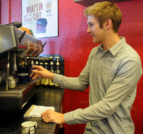 Jordan Allen prepares a cup of coffee for a client at Davinci's Coffee House, 2315 W. Willow Road. Allen, who graduated from high school two years ago, recently purchased the business. (Staff Photo by BONNIE VCULEK)
