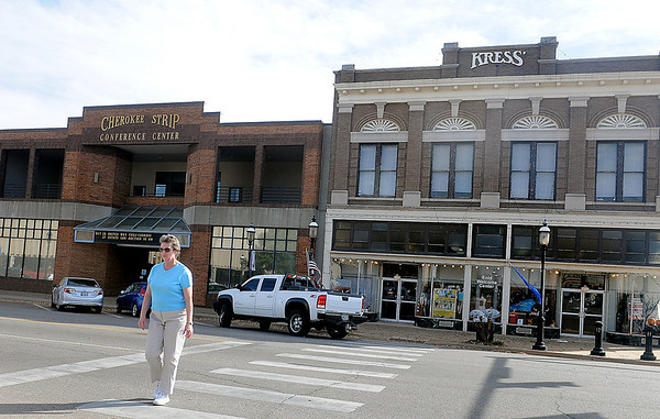 A pedestrian crosses Maine Street Tuesday near the Cherokee Strip Conference Center and Kress Building. As construction on the Renaissance Center project continues, city officials are considering locations for a downtown hotel location. (Staff Photo by BONNIE VCULEK)