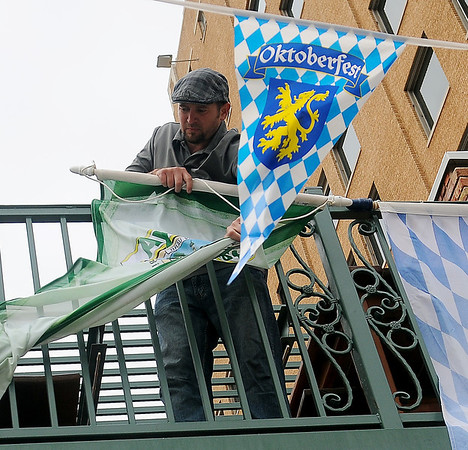 Donny Kovacs hangs Oktoberfest banners from the balcony at Callahan's Pub Friday. (Staff Photo by BONNIE VCULEK)