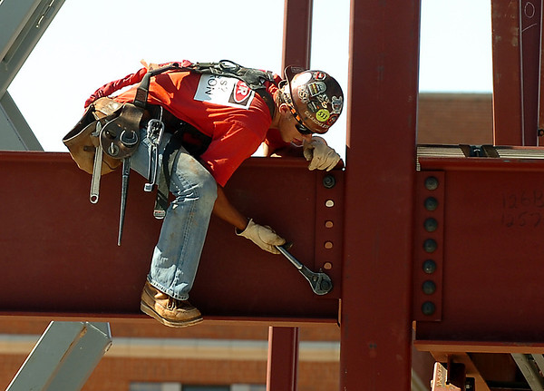 An iron worker tightens a nut on a beam Monday as construction continues on the University Center at Enid High School. (Staff Photo by BILLY HEFTON)
