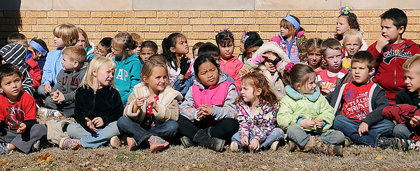 Taft Elementary School students listen and watch an Enid Police K-9 demonstration Friday. Enid Police Officers Chase Bouziden and Ryan Fuxa answered questions during the school's Red Ribbon event. (Staff Photo by BONNIE VCULEK)