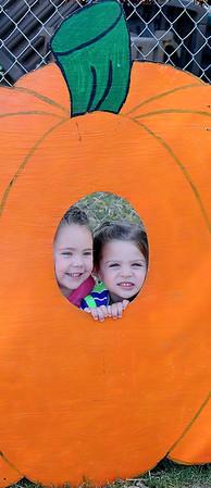 Madison Wolever (left) and Ashlynn Parker peer through a large pumpkin display Thursday at Christ United Methodist Church's Pumpkin Patch. (Staff Photo by BONNIE VCULEK)