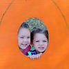 Madison Wolever (left) and Ashlynn Parker peer through a large pumpkin display Thursday at Christ United Methodist Church's Pumpkin Patch. (Staff Photo by BONNIE VCULEK)