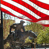 Boomer appears to ride under an American flag posted around the downtown square Monday to commemorate Columbus Day. (Staff Photo by BILLY HEFTON)