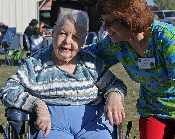 Junie Lebow (left) smiles as she watches the children play during Oktoberfest at The Commons Friday. Connie Yeager (right), activities assistant for The Commons, helped organize inflatables and food for the event. (Staff Photo by BONNIE VCULEK)