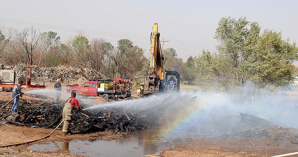 With the help of a crane operator, Pond Creek-Hunter and Nash Firefighters battle a fire east of Pond Creek Thursday. Oklahoma Highway Patrol closed U.S. 60 east of Pond Creek until firefighters could bring the blaze under control. (Staff Photo by BONNIE VCULEK)