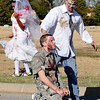A trio of zombies wait for runnners Tuesday at Vance Air Force Base during the base's 5k Zombie Run. (Staff Photo by BILLY HEFTON)
