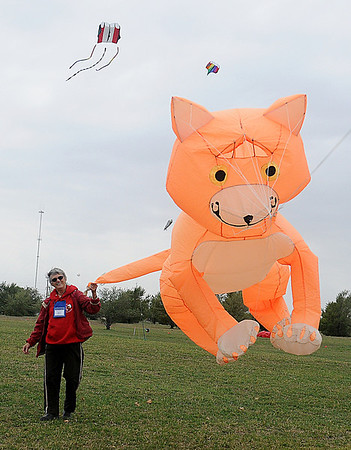 """Marti Dermer, from Stillwater, grabs her Peter Lynn """"Cat"""" kite by its tale Thursday during the American Kitefliers Association National Convention. The unique kite was designed and created in New Zealand. (Staff Photo by BONNIE VCULEK)"""