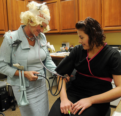 """Deedy Wichert (left) portrays actress Tippi Hedren from the 1963 Alfred Hitchcock movie """"The Birds"""" Wednesday as she takes Montse Gomez's blood pressure at Family Physicians. (Staff Photo by BONNIE VCULEK)"""