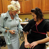 "Deedy Wichert (left) portrays actress Tippi Hedren from the 1963 Alfred Hitchcock movie ""The Birds"" Wednesday as she takes Montse Gomez's blood pressure at Family Physicians. (Staff Photo by BONNIE VCULEK)"