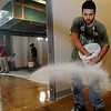 Skyler Mora broadcasts an epoxy floor product Thursday as workers complete the floor finish in the new Convention Hall kitchen and service corridor. The grand opening of the Renaissance event center is slated for November 18. (Staff Photo by BONNIE VCULEK)