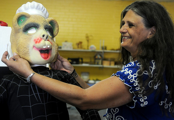 Judy Bohler places a Halloween mask on a Park Avenue Thrift mannequin Tuesday. The local business has several children's costumes available at discounted prices. (Staff Photo by BONNIE VCULEK)