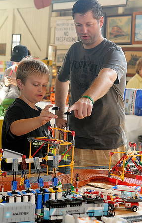 Brysen McDaniel and David Burrows check out one of the Lego Train Layout assessories during the Railroad Museum of Oklahoma Family Fun event Saturday. (Staff Photo by BONNIE VCULEK)