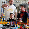 Jody Zook (back, left) explains his Dream Valley Lego Layout to Nik Ramos (center) and Collin Kroeker (right) Saturday at the Railroad Museum of Oklahoma event. (Staff Photo by BONNIE VCULEK)