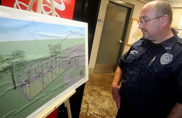 Enid Animal Control director Allen Elder glances at the plans for the exterior run expansion Saturday during the center's open house and ground-breaking ceremony. (Staff Photo by BONNIE VCULEK)