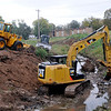 Construction equipment works on clearing the creek along Lakeside St. between Randolph and Broadway Wednesday. (Staff Photo by BILLY HEFTON)