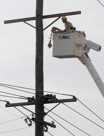 An Oklahoma Gas & Electric employee replaces high line support as Enid residents deal with power outages after heavy rains moved across Garfield County Friday. (Staff Photo by BONNIE VCULEK)