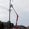 An OG&E crew repairs power outages along Cleveland Friday morning as the Enid Police Department assists. (Staff Photo by BONNIE VCULEK)