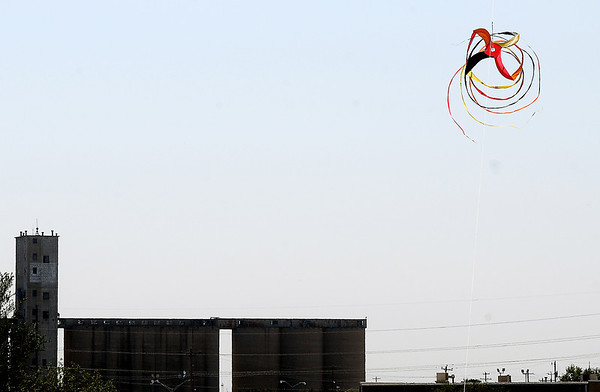 A grain storage facility appears (lower left) as a large snake kite spins in the air Monday during the opening day of American Kite Association National Convention in Enid. (Staff Photo by BONNIE VCULEK)