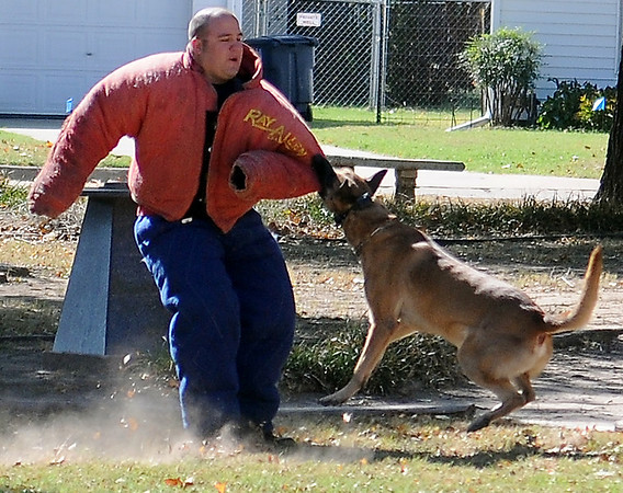 """Enid K-9 Police Officer Chase Bouziden (left) demonstrates the ferocious biting power of Duko during a """"Red Ribbon"""" demonstration for students at Taft Elementary School Friday. (Staff Photo by BONNIE VCULEK)"""