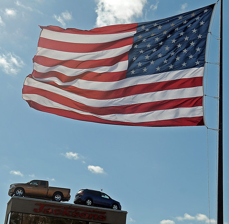 A massive American flag flaps in the wind at Jacksons of Enid as north winds gust in excess of 30 mph Thursday. Temperatures are expected to drop into the 30s tonight as the cold front arrives. (Staff Photo by BONNIE VCULEK)