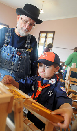 Luke Wheeler (right) concentrates as he learns table loom weaving techniques from Thomas Galbraith during Family Farm Day at the Cherokee Strip Regional Heritage Center and Humphrey Heritage Village Saturday, Oct. 26, 2013. (Staff Photo by BONNIE VCULEK)