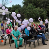 Audience members watch as the wind takes away purple balloons released in rememberance of female victims of domestic violence during a ceremony at the Enid YWCA Tuesday. (Staff Photo by BILLY HEFTON)